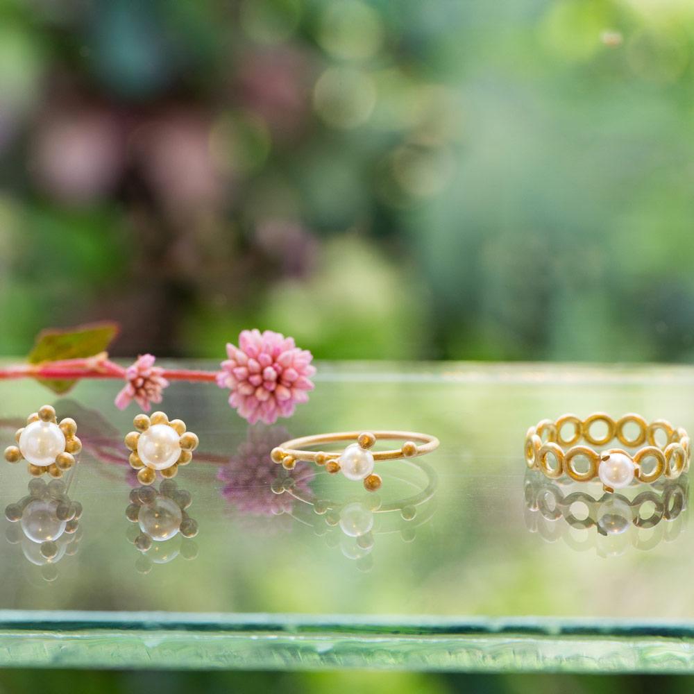 屋久島しずくギャラリーのディスプレイ ゴールドのリング パール ピアス 屋久島の緑バック 屋久島でつくる結婚指輪