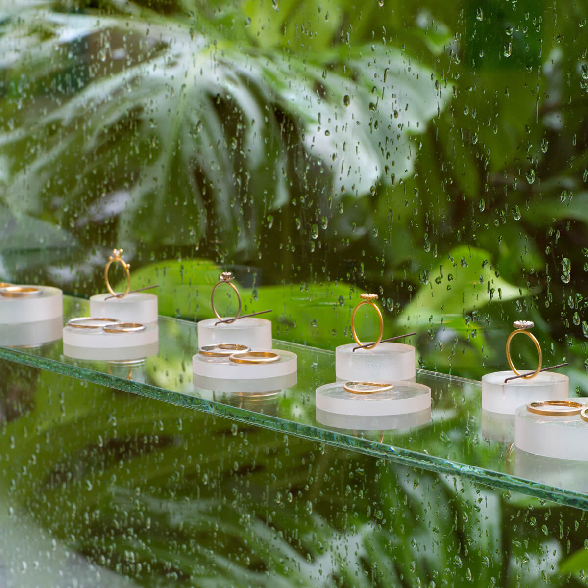 屋久島しずくギャラリー ジュエリーのディスプレイ 奥に屋久島の緑 屋久島でつくる結婚指輪 オーダーメイドマリッジリングの販売
