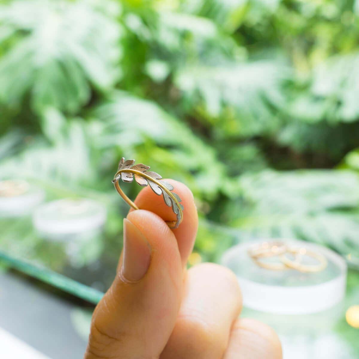 屋久島しずくギャラリーのディスプレイ 屋久島の緑バック シダの指輪手に取って プラチナ、ゴールド 屋久島でつくる結婚指輪