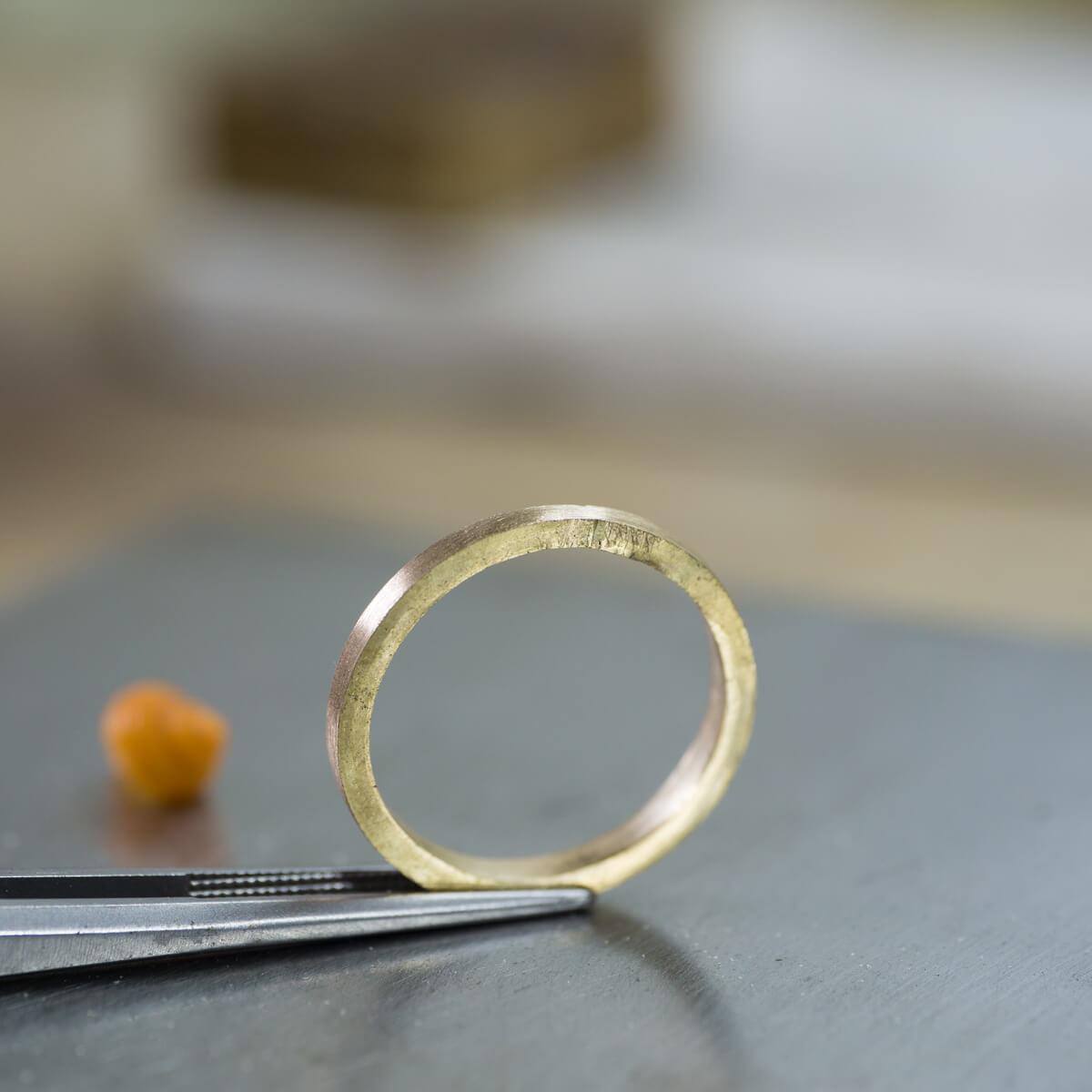 オーダーメイドマリッジリングの制作風景 ジュエリーのアトリエ シャンパンゴールドのリング 奥に見える屋久島の貝殻 屋久島でつくる結婚指輪