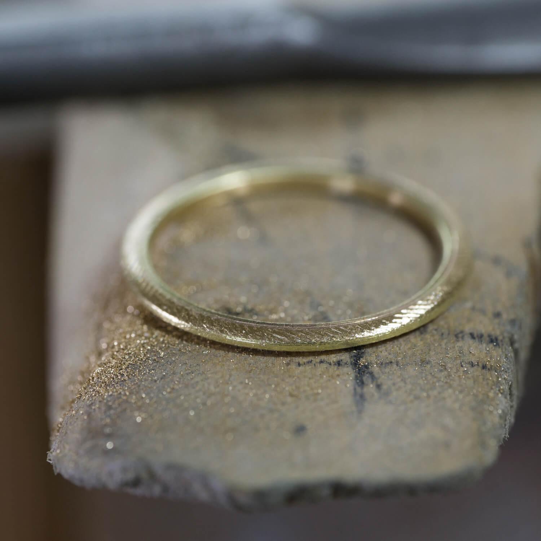 オーダーメイドマリッジリングの制作風景 ジュエリーのアトリエ 作業場に指輪、鉄鋼ヤスリ、削り中 ゴールド 屋久島で作る結婚指輪