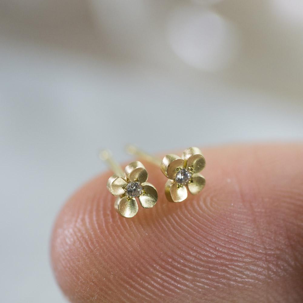 ゴールドのピアス ダイヤモンド 屋久島の菜の花モチーフ 指に乗せて