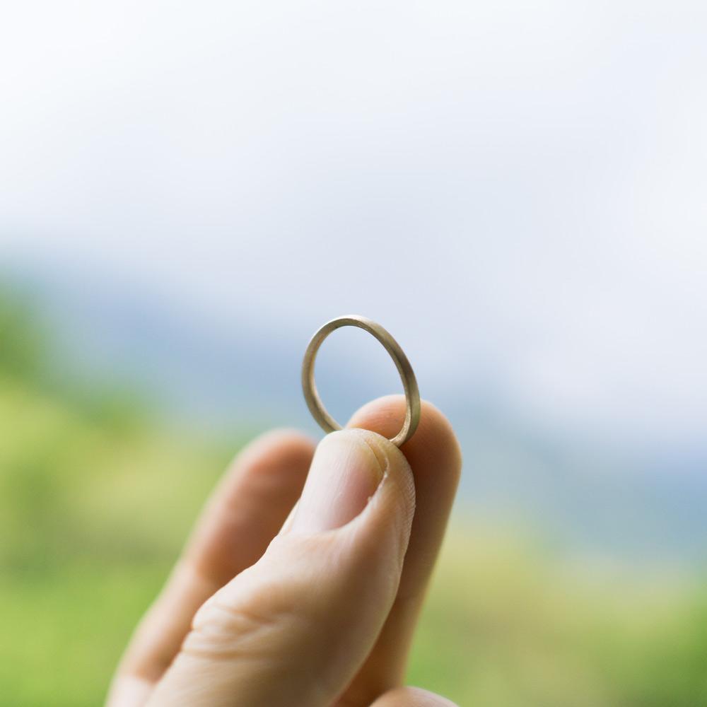屋久島の緑バック ゴールドの指輪 手に持って オーダーメイドのマリッジリング