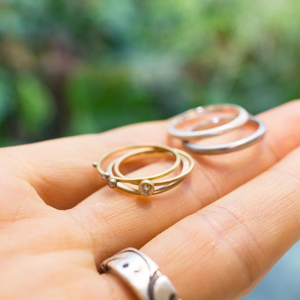 手のひらの上 結婚指輪のサンプル ゴールド、シルバー、ダイヤモンド 屋久島の緑バック