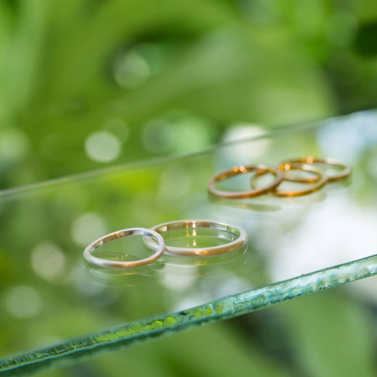 屋久島しずくギャラリー、ジュエリーのディスプレイ シルバーゴールドリング オーダーメイド結婚指輪のサンプル 屋久島の緑バック 屋久島でつくる結婚指輪