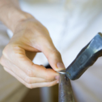 オーダーメイドマリッジリングの制作風景 ジュエリーの工房 手に金槌、指輪 プラチナ 屋久島でつくる結婚指輪
