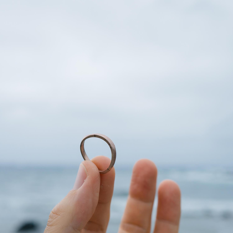 屋久島の海バック オーダーメイドマリッジリングを手に ゴールド 屋久島でつくる結婚指輪