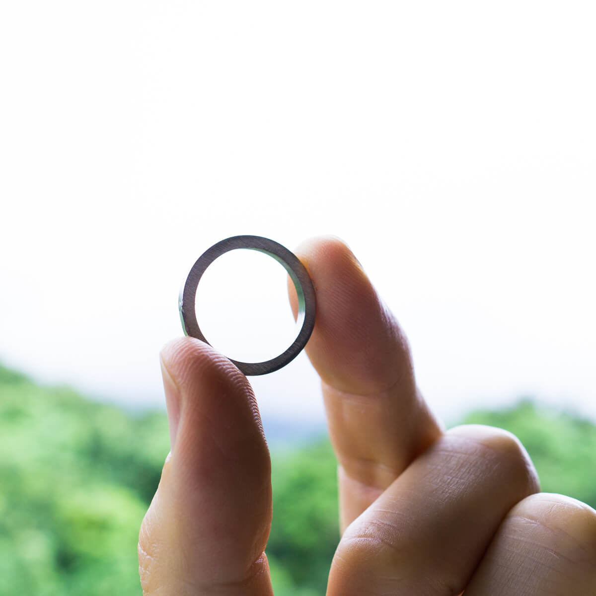 オーダーメイドジュエリーの制作風景 手に指輪 プラチナ 屋久島の山々バック 屋久島でつくる結婚指輪