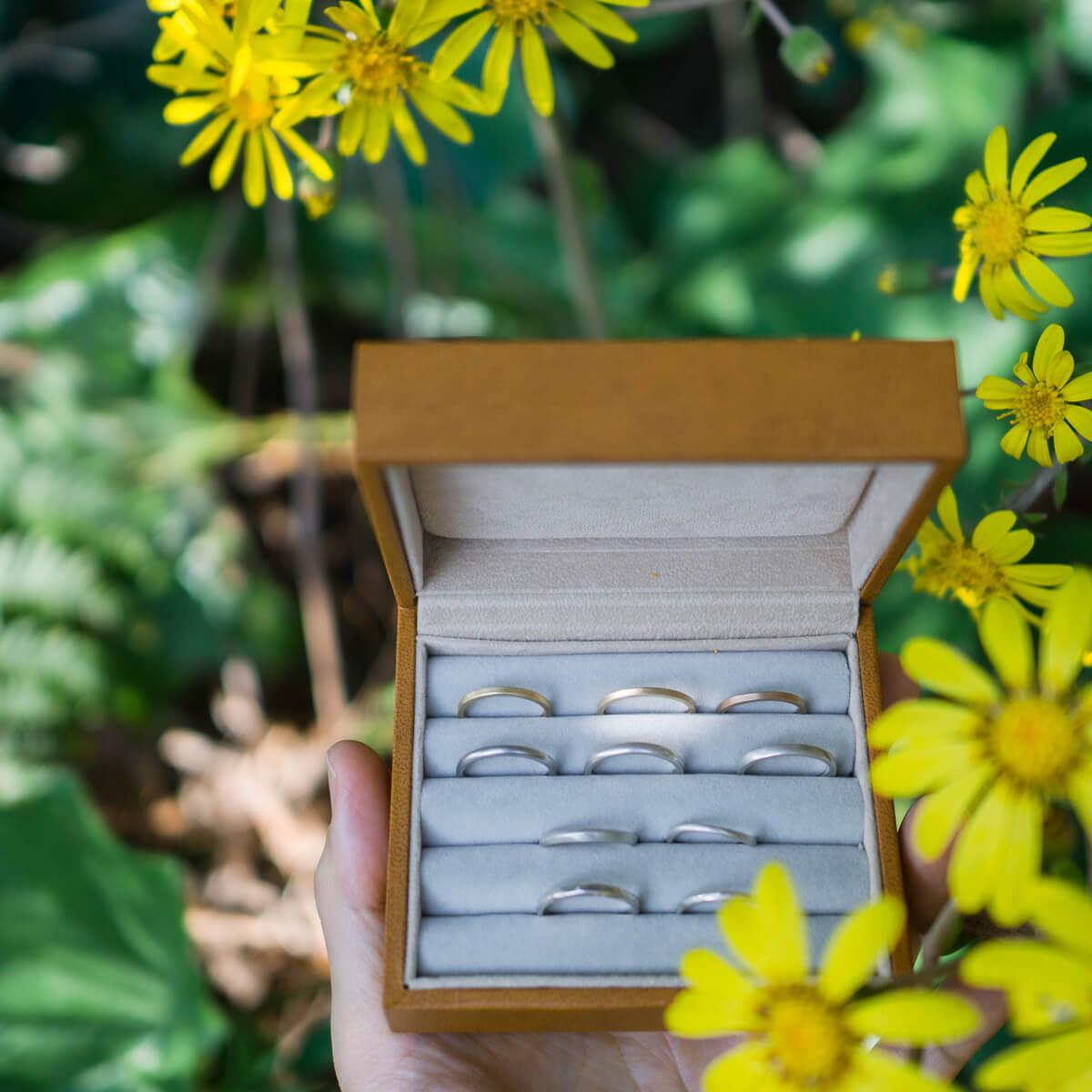 屋久島のツワブキバック オーダーメイドマリッジリングのサンプル ケースの中 手に持って 屋久島でつくる結婚指輪