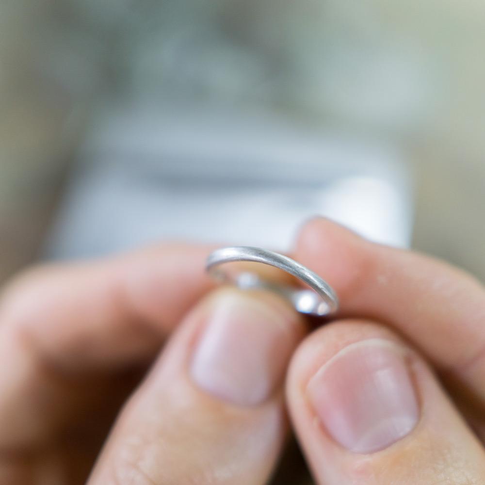 シルバーのサンプルリングを手に オーダーメイドマリッジリングの制作風景 ジュエリーのアトリエ 作業場に指輪  屋久島で作る結婚指輪