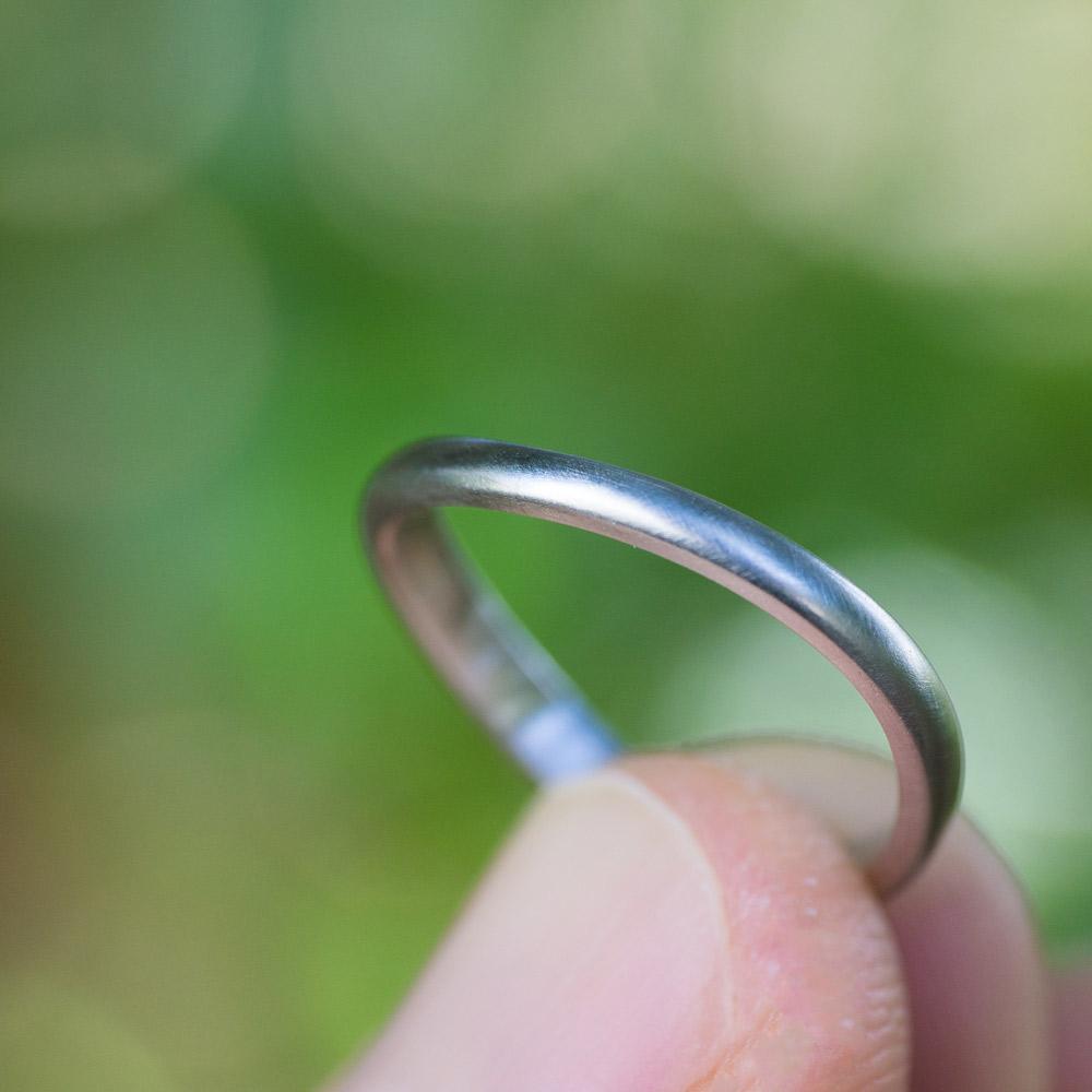 場面2 オーダーメイドマリッジリングの制作風景 屋久島の緑バック 手に指輪 プラチナ 屋久島で作る結婚指輪