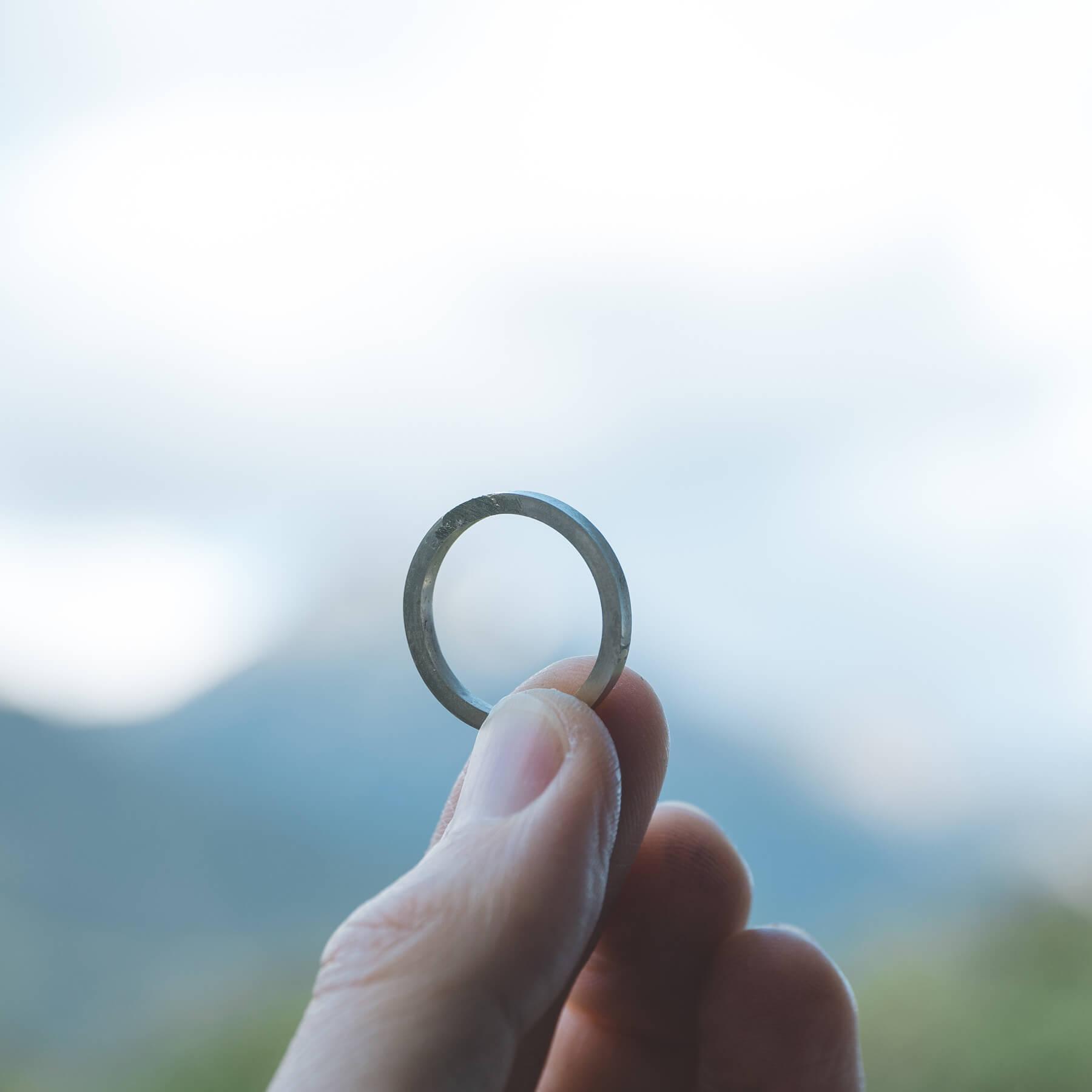 制作途中のオーダーメイドマリッジリング 手に持って 屋久島の山々バック 屋久島でつくる結婚指輪