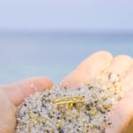 屋久島の海 手のひらの上に砂、ゴールドの結婚指輪 屋久島で作る結婚指輪