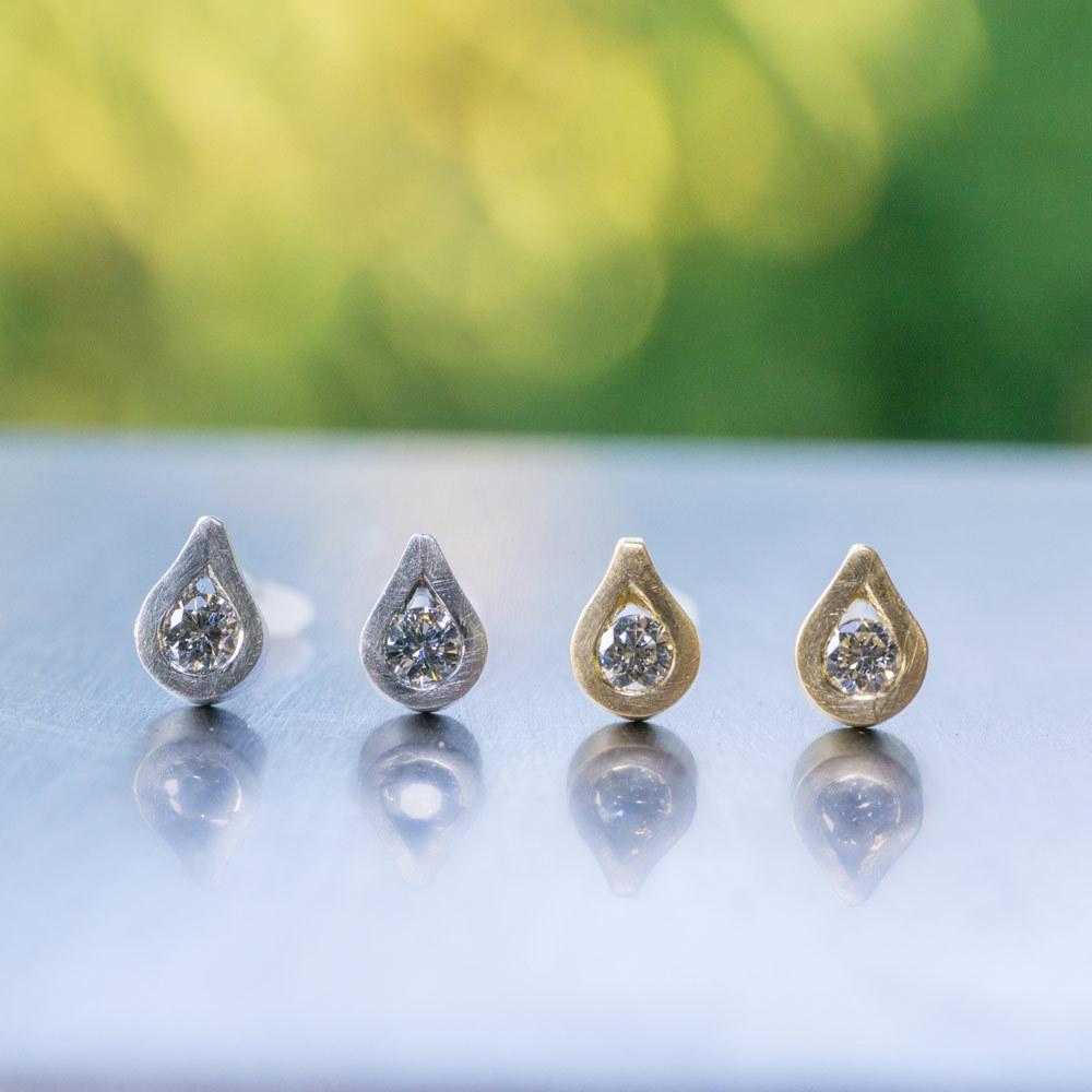 しずく型のピアス 作業台の上 屋久島の緑バック ダイヤモンド、ゴールド、プラチナ