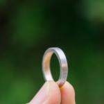 結婚指輪の制作風景 ゴールド、プラチナリング 屋久島の緑バック手に持って 屋久島で作る結婚指輪
