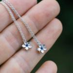 お花のネックレス 手に持って 屋久島の緑バック シルバー、ゴールド