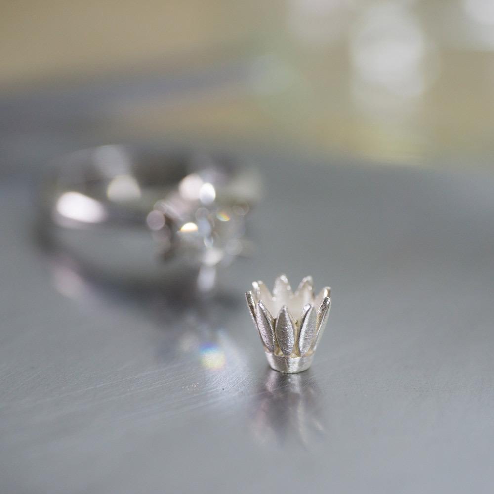 花びらの石枠 奥に見えるプラチナのエンゲージリング、ダイヤモンド オーダーメイドのリメイクジュエリー